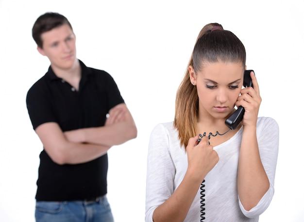 Hombre celoso detrás de las mujeres que hablan por teléfono.