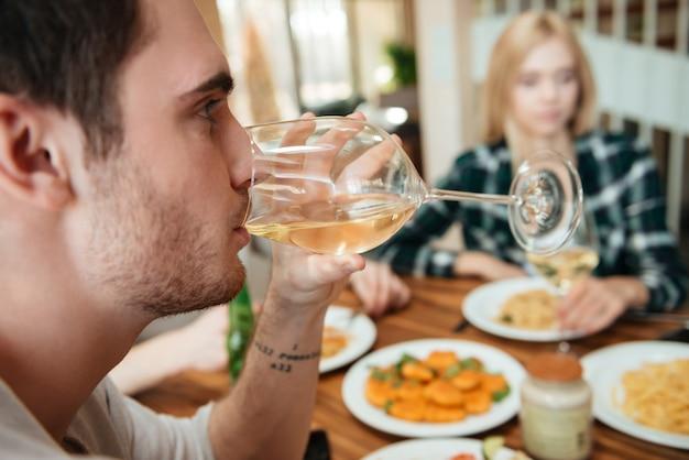 Hombre cenando y bebiendo vino con amigos en la cocina