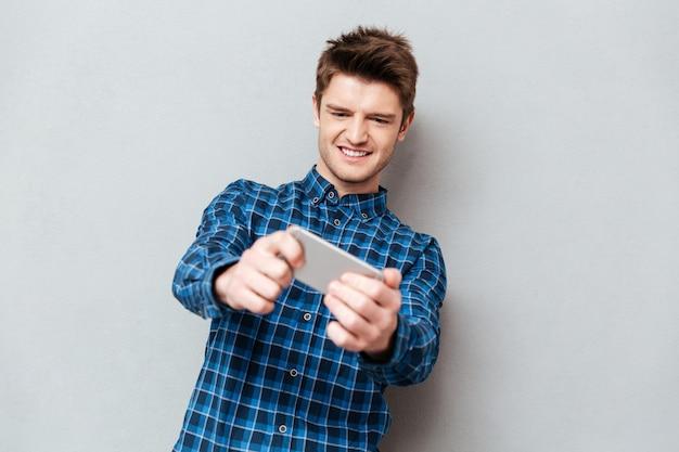 Hombre centrado en el juego en el teléfono inteligente