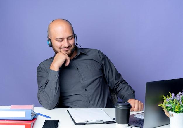 Hombre de centro de llamadas calvo joven complacido con auriculares sentado en el escritorio con herramientas de trabajo mirando hacia abajo en el portapapeles con la mano en el mentón aislado sobre fondo púrpura