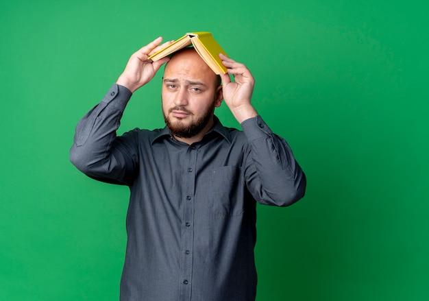 Hombre de centro de llamadas calvo joven confidente que sostiene el libro en la cabeza aislada en verde con espacio de copia