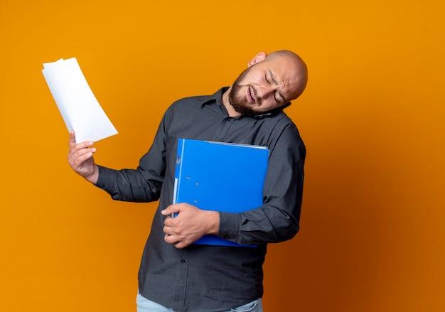 Hombre de centro de llamadas calvo joven disgustado sosteniendo carpeta y documentos y hablando por teléfono sosteniendo el teléfono en el hombro aislado sobre fondo naranja con espacio de copia