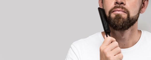 Hombre cepillándose la barba con espacio de copia