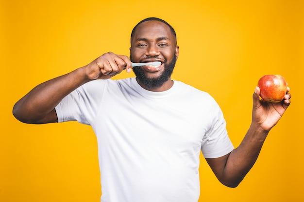 Hombre con cepillo de dientes. imagen de un joven africano sin camisa, sosteniendo un cepillo de dientes con pasta de dientes y manzana, sonriendo