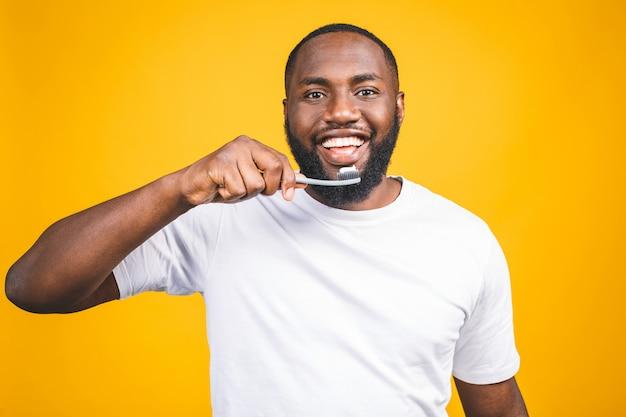 Hombre con cepillo de dientes. imagen del joven hombre africano sin camisa sosteniendo un cepillo de dientes con pasta de dientes y sonriendo