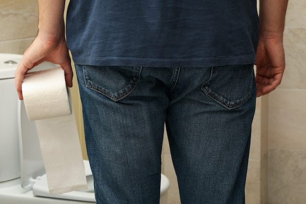Un hombre se para cerca del inodoro y sostiene papel higiénico.