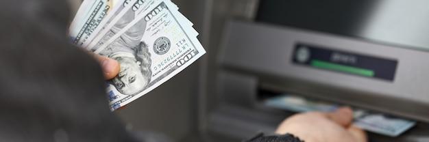 El hombre se para cerca de la terminal y retira dólares en efectivo. limite los retiros de efectivo durante la cuarentena. retiro de efectivo automatizado con tarjetas de pago. pago de bienes y servicios a través de un cajero automático
