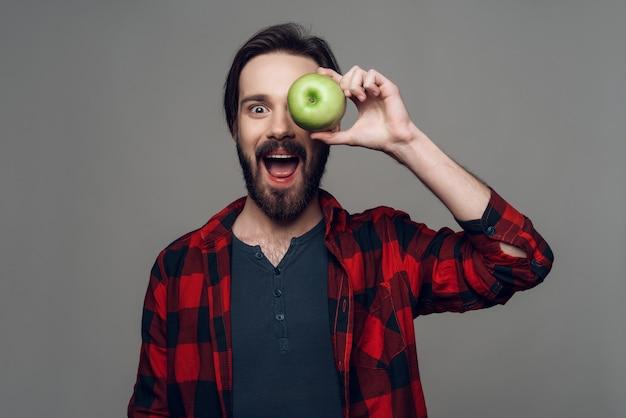 El hombre cerró los ojos con una manzana y se rió.