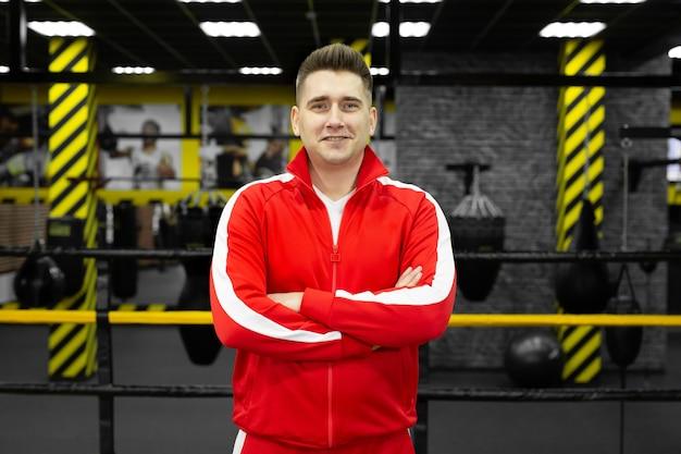 Hombre en un chándal rojo posa y se divierte en el ring de boxeo