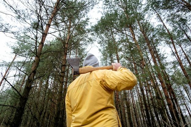 Hombre de chaqueta amarilla en bosque con hacha
