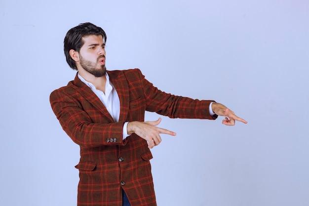 Hombre con chaqueta de cuadros apuntando a algo a la derecha y hablando de ello.