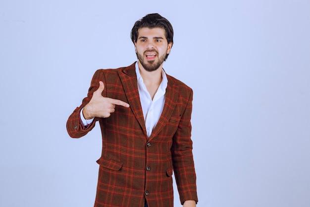 Hombre en chaqueta de cuadros apuntando a sí mismo y actuando.