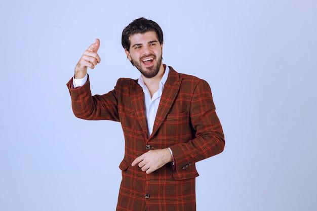 Hombre con chaqueta de cuadros dando un discurso en la escena y presentando algo arriba.