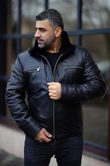 Un hombre con una chaqueta de cuero en el fondo de la metrópoli. apariencia oriental de la modelo.