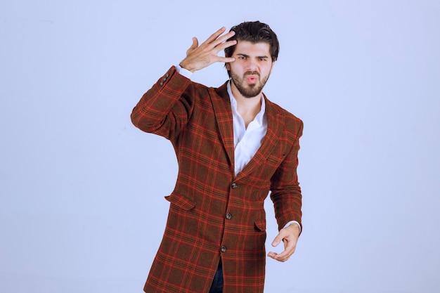 El hombre con chaqueta marrón parece confundido y trata de explicarse.