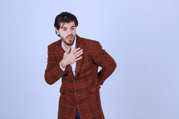 Hombre de chaqueta marrón saludando a alguien.