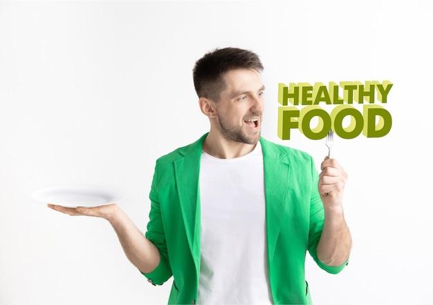 Hombre de chaqueta verde con la gente aislada en blanco. modelo masculino sosteniendo un plato con letras de la palabra comida sana. elegir una alimentación saludable, una dieta, una nutrición orgánica y un estilo de vida amigable con la naturaleza.