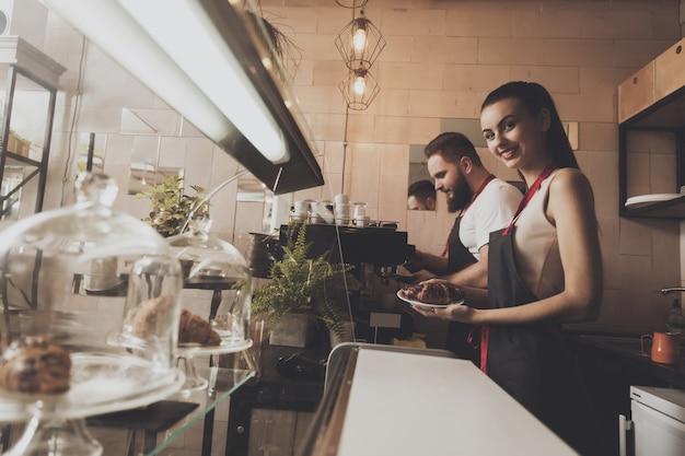 Hombre y chica guapa barista detrás del mostrador.