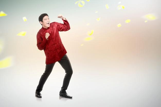 Un hombre chino asiático en traje de cheongsam celebra el año nuevo chino