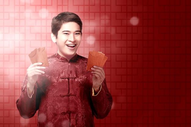 Un hombre chino asiático en un vestido cheongsam con sobres rojos