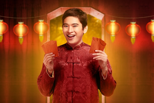 Hombre chino guapo en ropas tradicionales con angpao