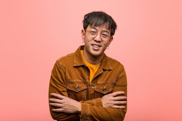 Hombre chino joven que llevaba una chaqueta cruzando los brazos, sonriendo y relajado.
