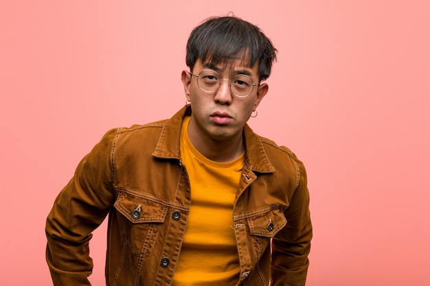Hombre chino joven que llevaba una chaqueta regañando a alguien muy enojado