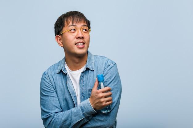 Hombre chino joven que sostiene una botella de agua que sonríe confiada y que cruza los brazos, mirando para arriba