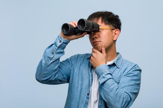 Hombre chino joven que sostiene los prismáticos que duda y confuso