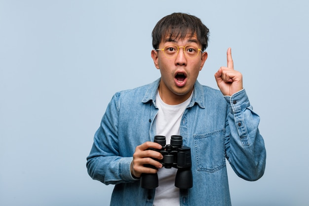 Hombre chino joven que sostiene los prismáticos que tienen una gran idea, concepto de creatividad