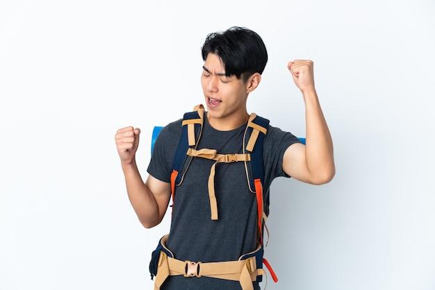 Hombre chino montañero con aislado en la pared blanca celebrando una victoria