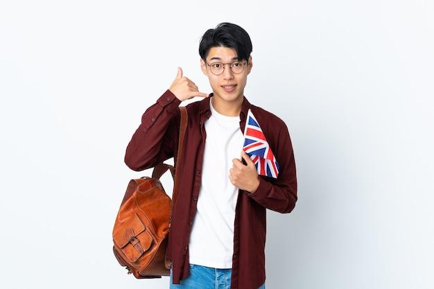 Hombre chino sosteniendo una bandera del reino unido aislada en la pared púrpura haciendo gesto de teléfono. llámame señal