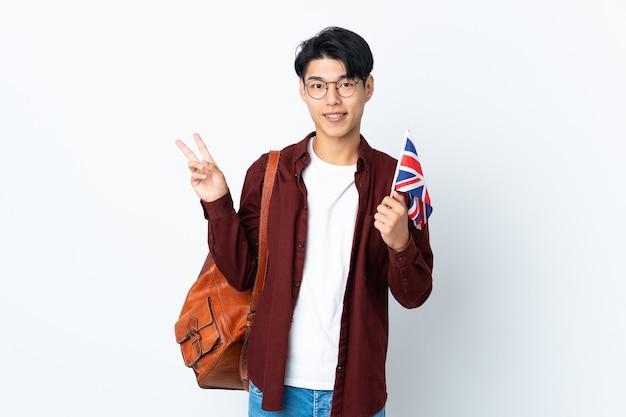 Hombre chino sosteniendo una bandera del reino unido aislado en la pared púrpura sonriendo y mostrando el signo de la victoria