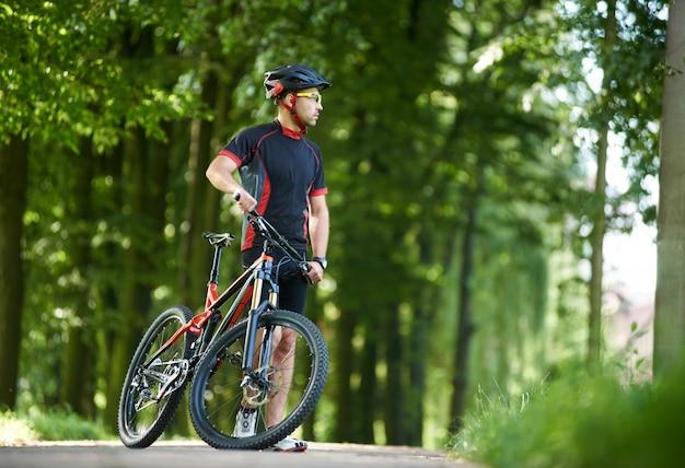 Hombre ciclista profesional en ropa de ciclismo y casco mirando a lo lejos