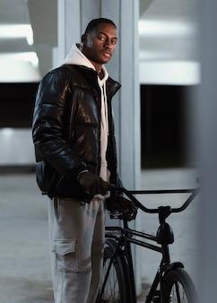 Hombre ciclista de vista lateral sosteniendo su bicicleta