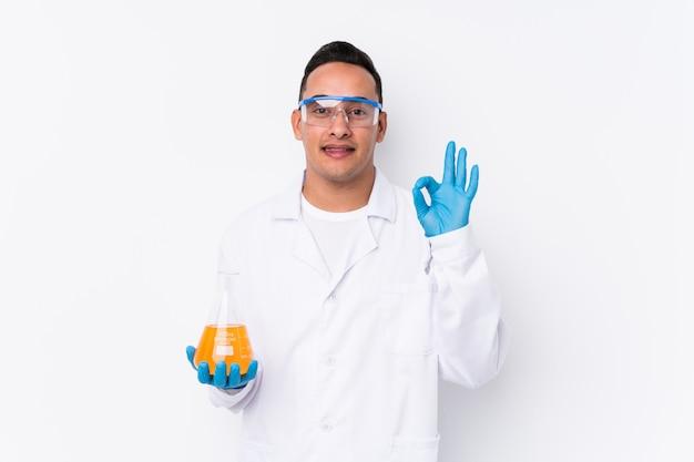 El hombre científico latino joven aisló alegre y confiado que mostraba gesto aceptable.