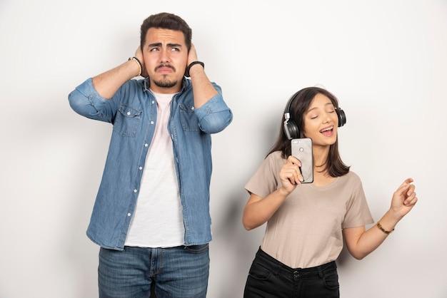 El hombre cierra los oídos mientras la mujer canta con todo su corazón.