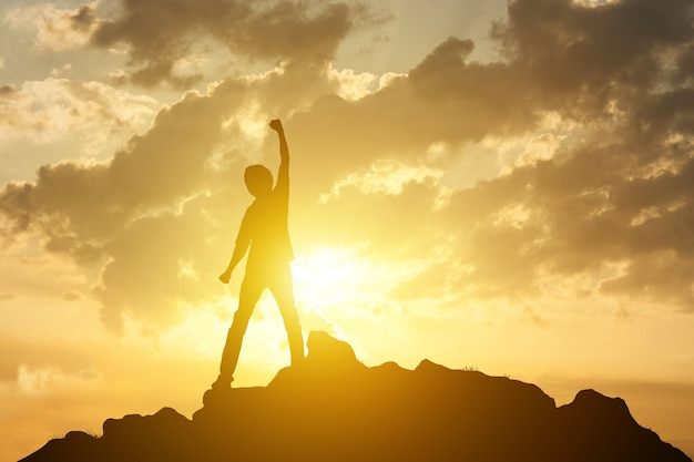 Hombre en la cima de la montaña y el concepto de éxito de ganador de fondo de amanecer o puesta de sol