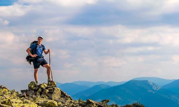 Hombre en la cima de la montaña. escena emocional hombre joven con mochila de pie con las manos levantadas en la cima de una montaña y disfrutar de vistas a la montaña. excursionista en la cima de la montaña. concepto de deporte y vida activa.
