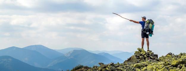 Hombre en la cima de la montaña. escena emocional hombre joven con mochila