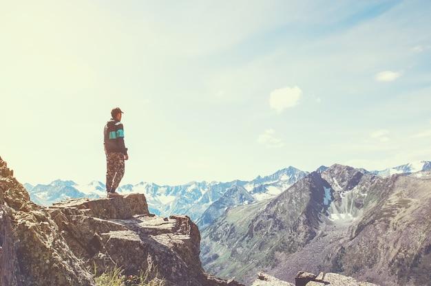 Un hombre está en la cima de una montaña y mira hacia el valle donde el río fluye desde el lago. entonado
