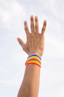 Hombre con cinta en colores lgbt en mano y cielo azul.