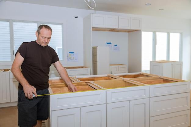 Hombre con cinta métrica para medir el tamaño en la cocina moderna para mejoras para el hogar.