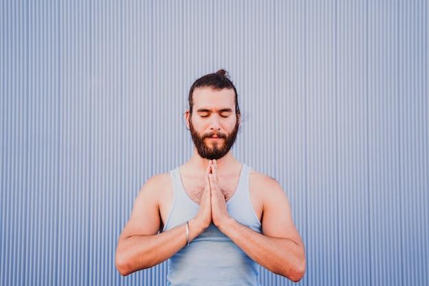 Hombre en la ciudad practicando deporte de yoga
