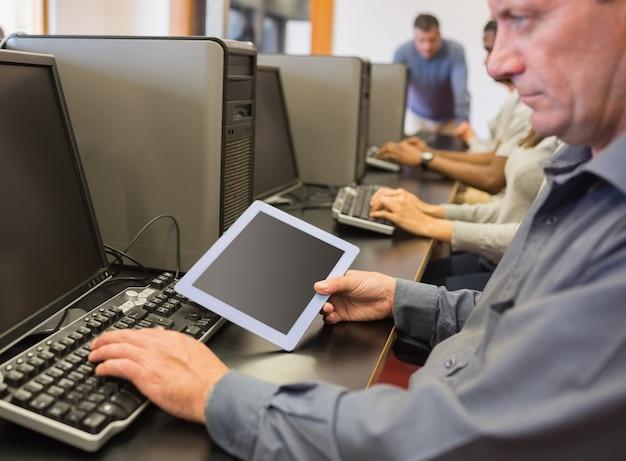 Hombre en clase de informática mirando tablet pc