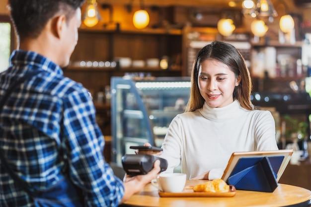 Hombre cliente asiático pagando con tarjeta de crédito a través de tecnología nfs sin contacto a asian barista