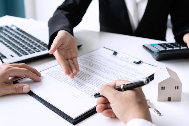 El hombre del cliente está firmando un contrato de arrendamiento de alquiler o un contrato de compraventa