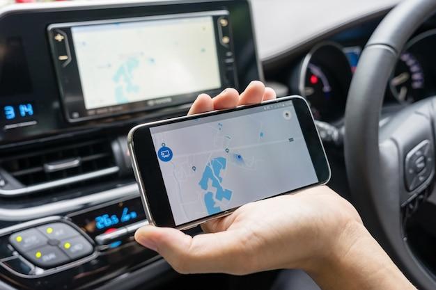 Hombre en el coche y sosteniendo un teléfono móvil negro con navegación por gps del mapa, entonado al atardecer.