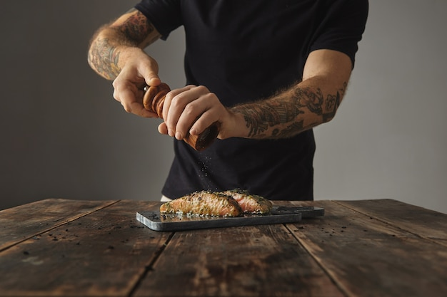 El hombre cocina comida saludable en la mesa de madera rústica, pimientos dos piezas crudas de salmón en salsa de vino blanco con especias y hierbas presentadas en la cubierta de mármol preparada para parrilla