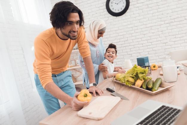 El hombre está cocinando detrás de él, de pie a su esposa en hijab e hijo.